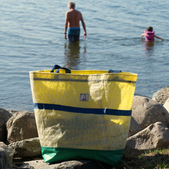Beach bag on the rocks at the waters edge, grandpa and granddaughter wading out into the water in the background
