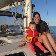 Ayla and young daughter sitting on cabin top of sailboat, Ruya, beautiful sunny day on Lake Ontario