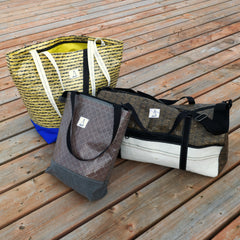 beach bag, duffel, zippered tote all made with high performance sail materials pictured on a wooden dock