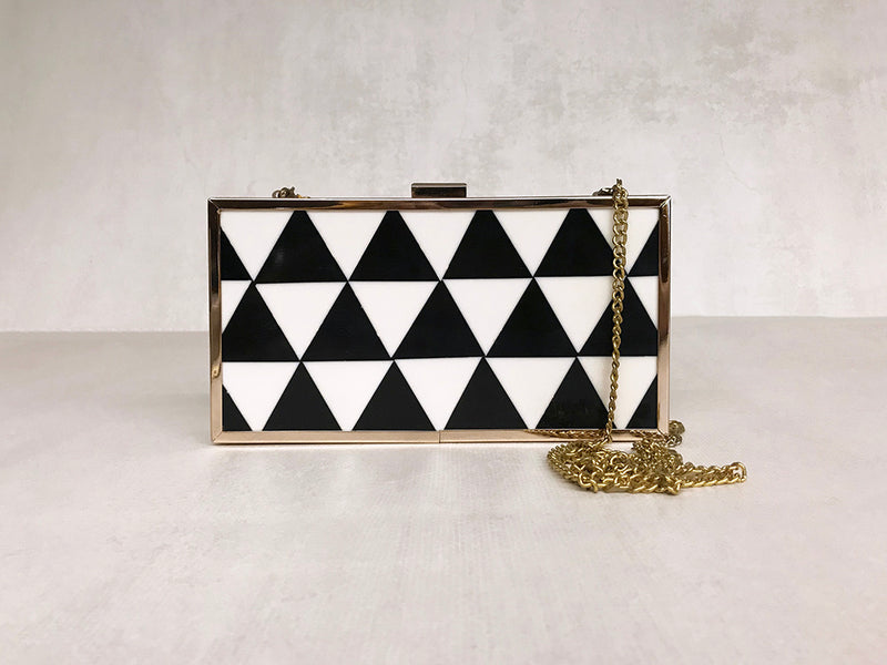 an acrylic geometric black and white clutch with gold metal rim and chain _ online gifts for her