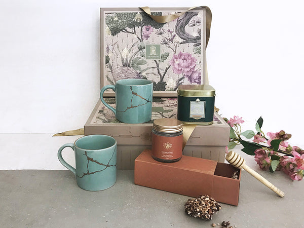 An ideal gifts for couple, contains a set of 2 handmade ceramic cups with kintsugi art gold print, a small jar of pure natural honey, a box of masala chai , a handcrafted wooden honey dipper and a box of chocolate almond florentine.