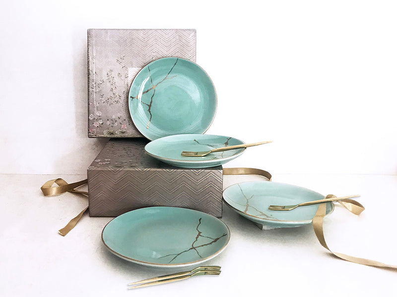 Set of 4 blue ceramic dessert plates with gold decal paired with a set of 4 handmade brass forks.
