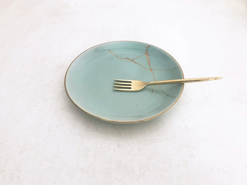A set of blue ceramic plate with gold decal kintsugi art print and a handmade brass fork.