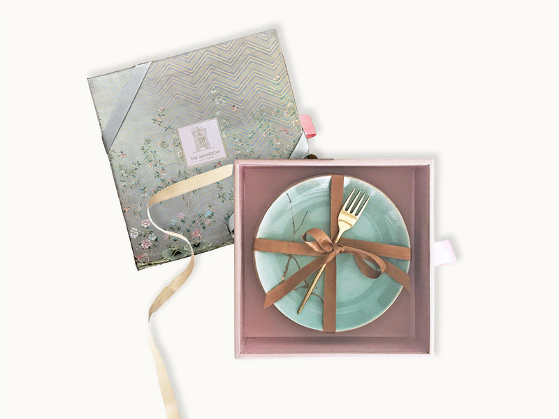 Kintsugi grace gift box contains a set of 4 ceramic plates with gold decal print and brass fork.