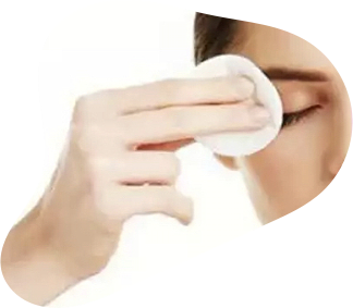 woman dubbing her eyelids with cotton