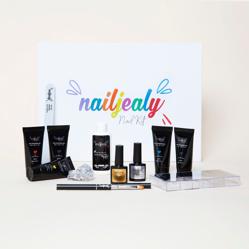 Picture of a white box with the NailJealy logo in the middle. In front of this, there are 5 black polygel bottles, two base and top coat bottles, a larger white bottle containing slip solution, alongside nail art and polygel application accessories.