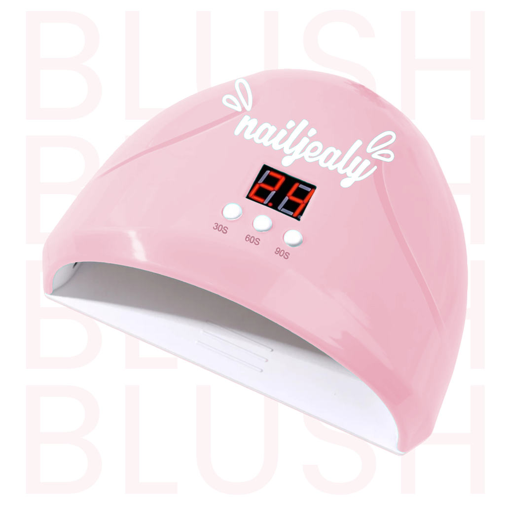 Image of a blush coloured LED nail lamp with a white NailJealy logo. The background is white with the word 'BLUSH' repeating in capitals.