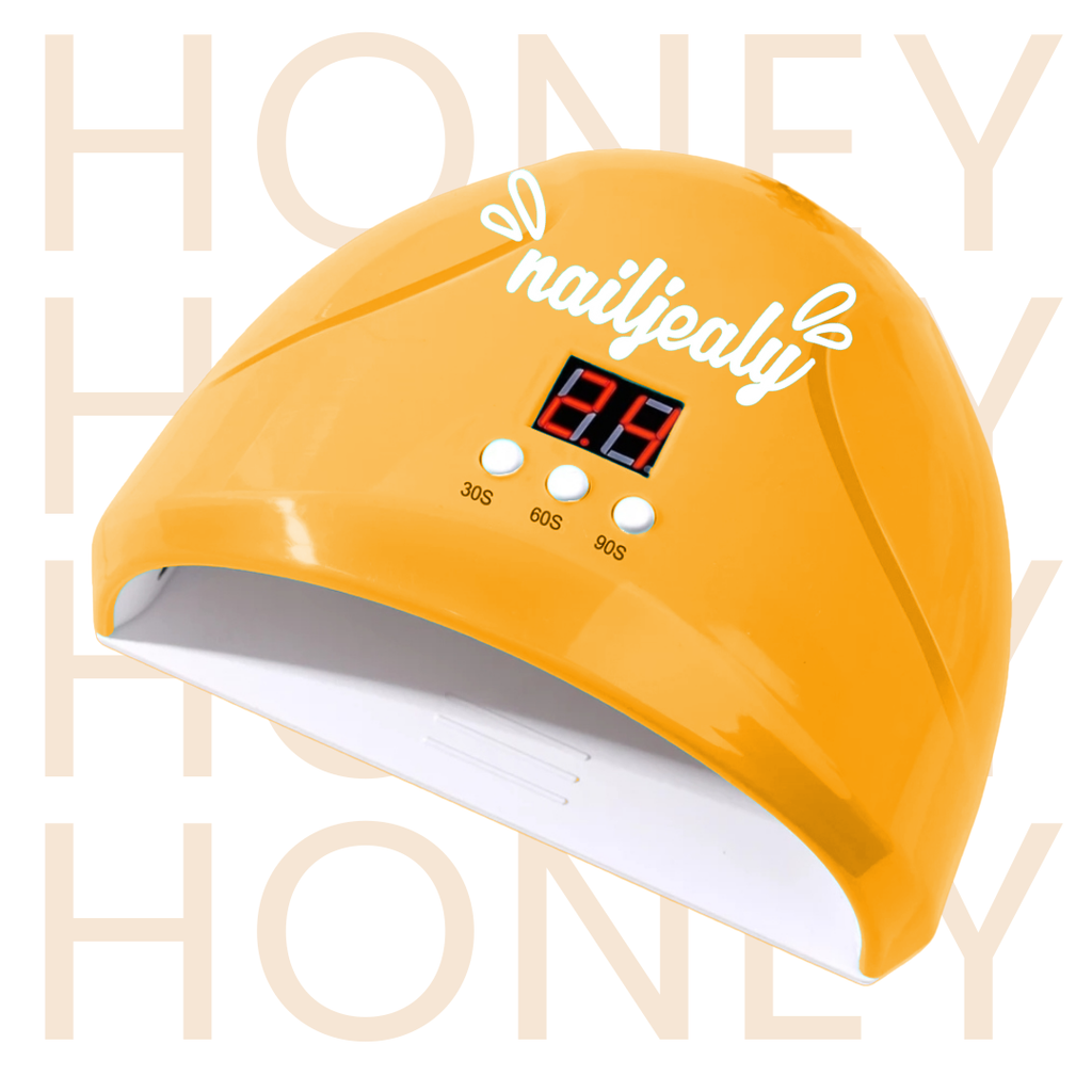 Image of a honey coloured LED nail lamp with a white NailJealy logo. The background is white with the word 'HONEY' repeating in capitals.