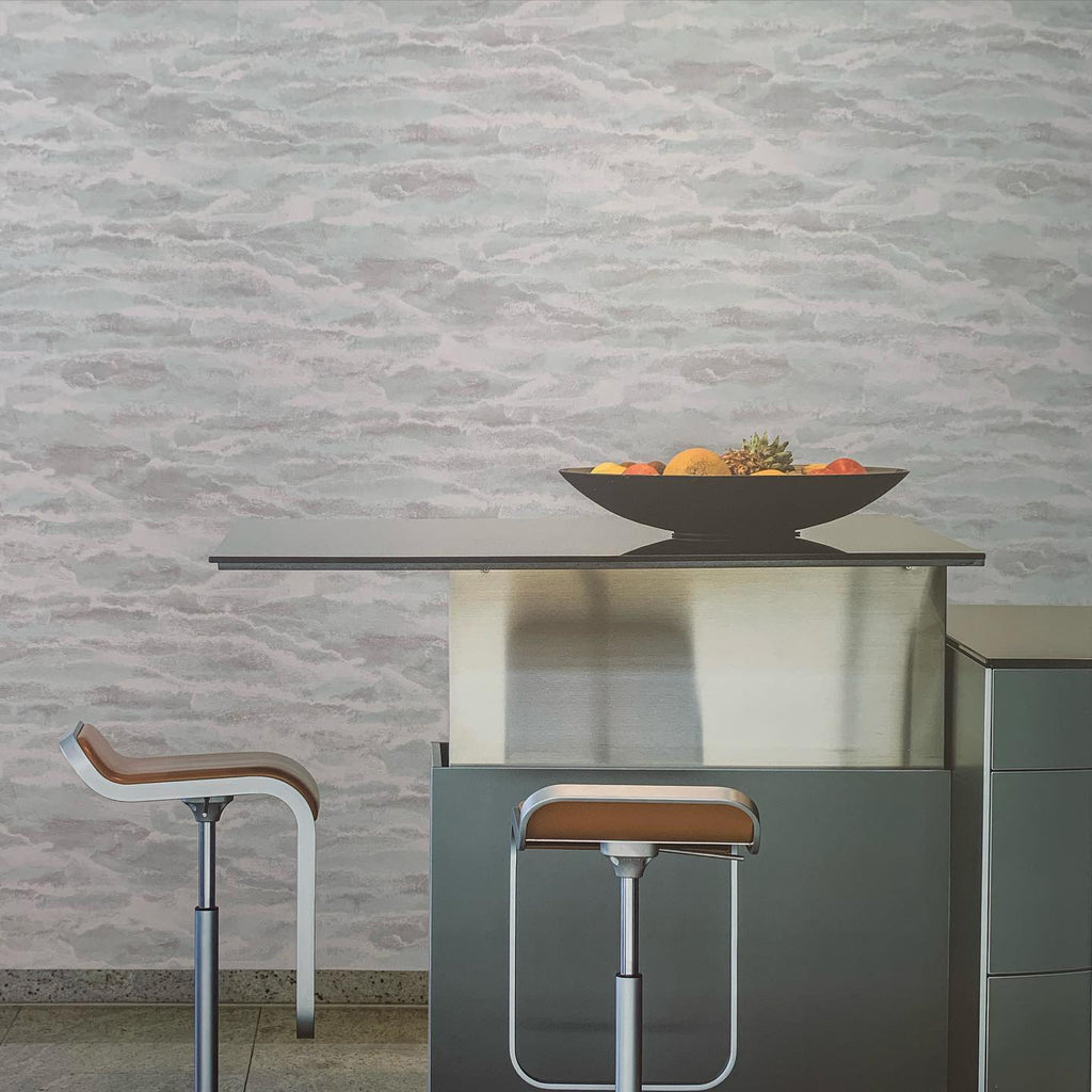 Two stools in front of counter with bowl of fruit and wall with patterned wallpaper in the background