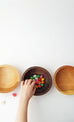 little hand taking jellybeans from dark wood bowl by Willful