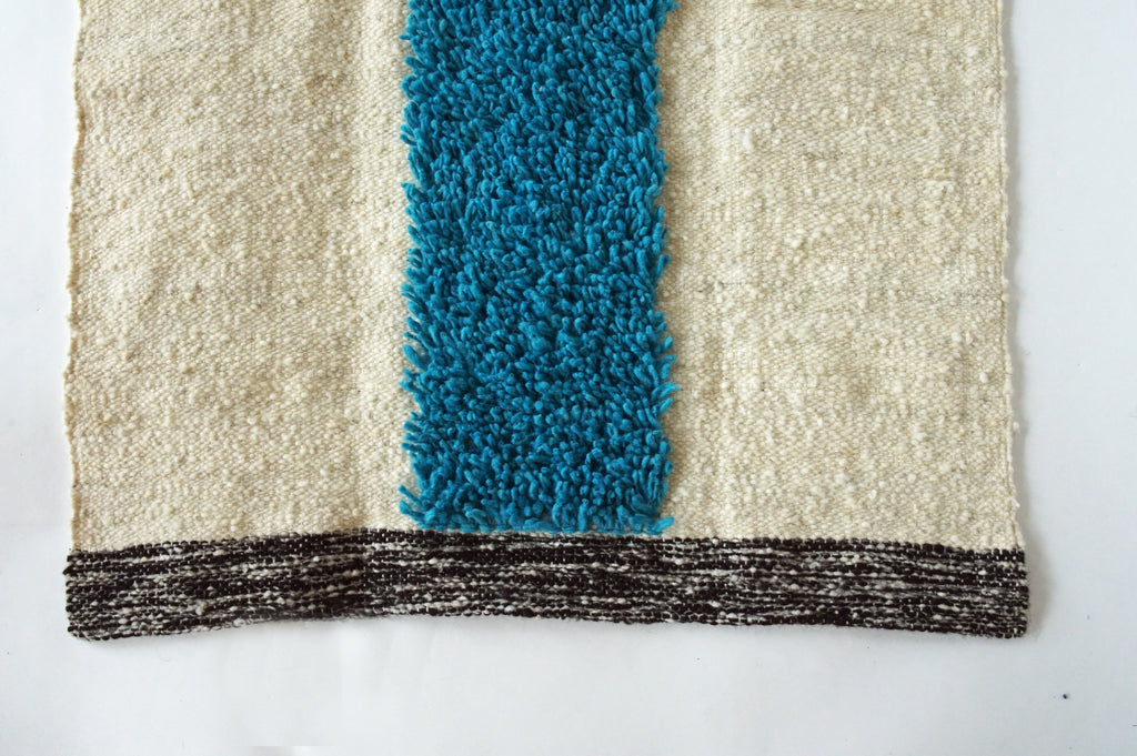 Detail of turquoise stripe natural wool rug by willful g