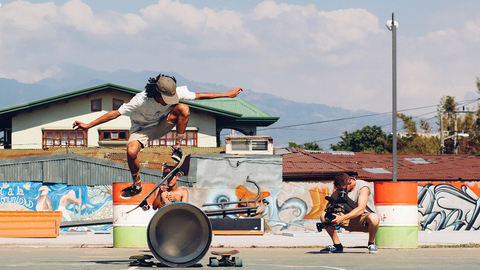 man ollies over trash can