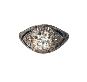 From our estate & antique collection, this Art Deco style engagement ring features a prong-set Old European cut diamond center. The handmade dome mounting is crafted of platinum featuring a mix of 20 natural and imitation blue sapphires, 52 Old European cut diamonds, ornate pierced filigree, and milgrain edges.  Total center diamond weight: 1.61ct  Color: K–L  Clarity: VS2  Total surrounding diamond weight: 0.33ct  Color: H–J  Clarity: SI1–I1  Ring size: