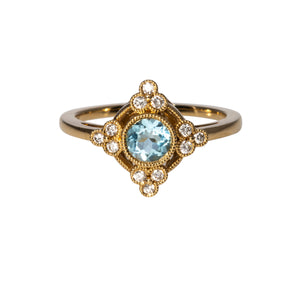 This ring features a blue topaz center surrounded by four trios of diamonds bezel set in 18K yellow gold with milgrain edges.  Total blue topaz weight: 0.54ct  Total diamond weight: 0.18ct