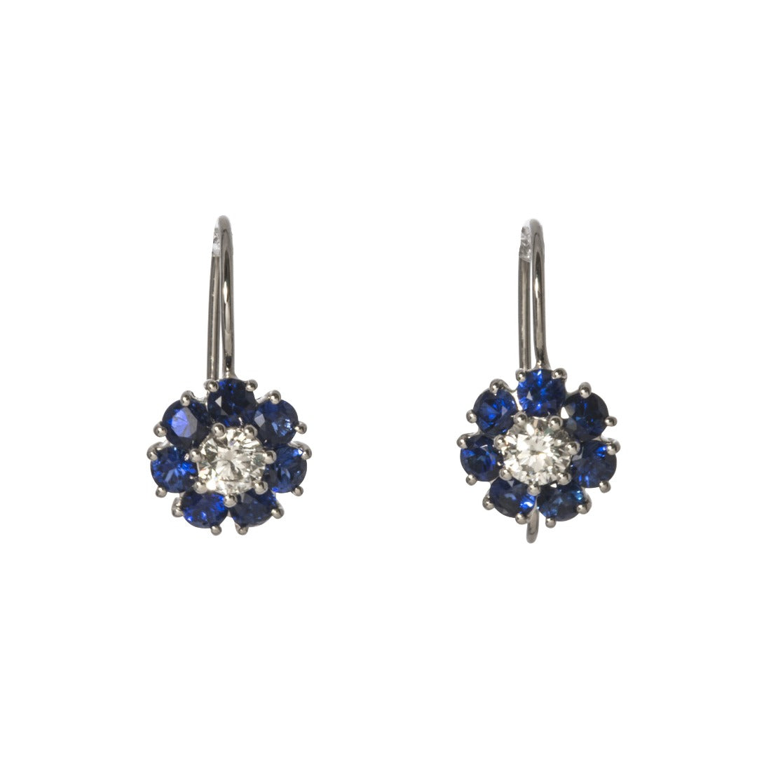This pair of floral drop earrings feature a round brilliant diamond center surrounded by blue sapphires set in 14K white gold with wire backs.  Total sapphire weight: 1.40ct  Total diamond weight: 0.36ct  Length: 18mm