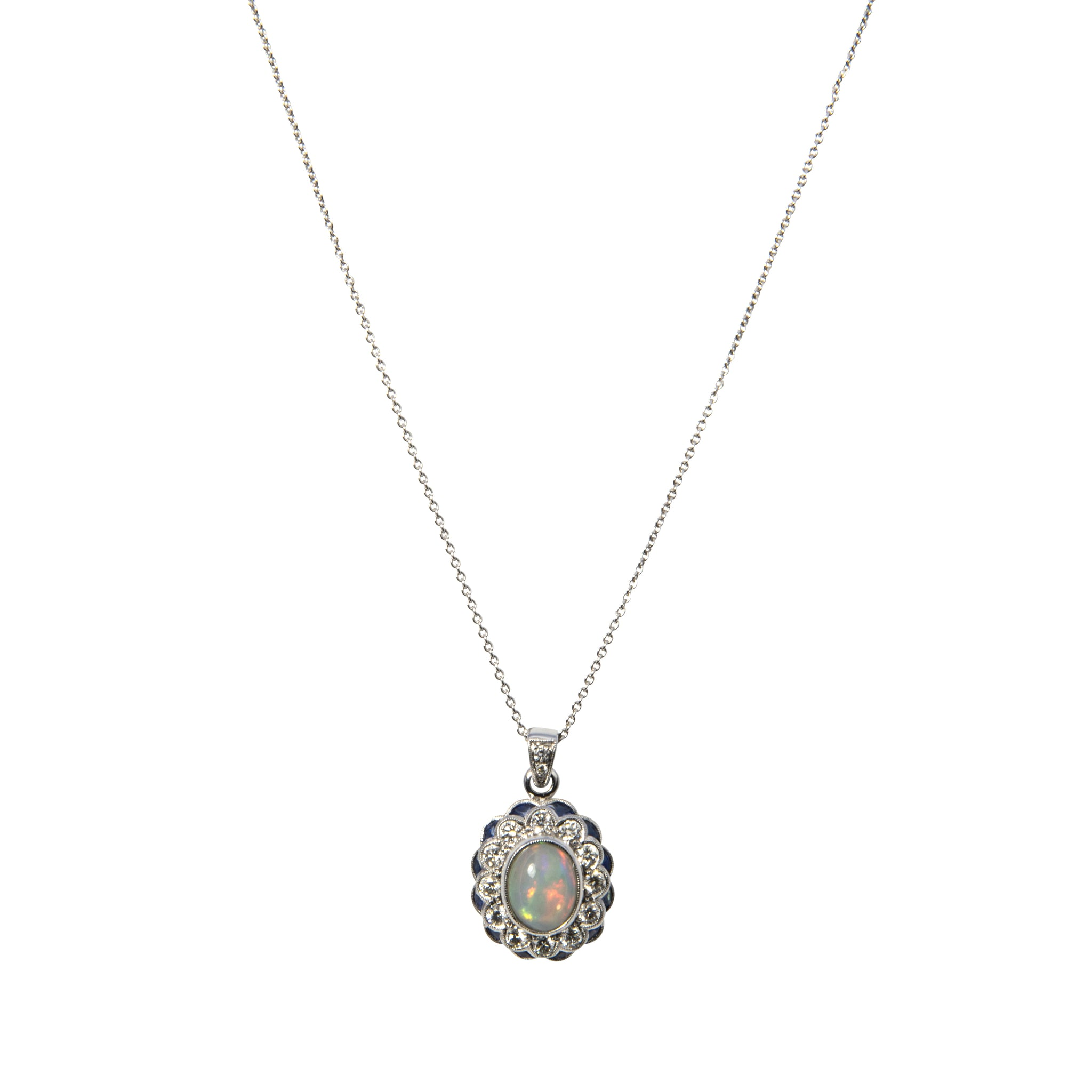 This necklace features a pendant with an oval cabochon opal surrounded by 12 round brilliant diamonds and 12 fantasy cut blue sapphires, as well as 2 round brilliant diamonds accenting the bail, all bezel set in 14K white gold with milgrain edges on an adjustable white gold chain.