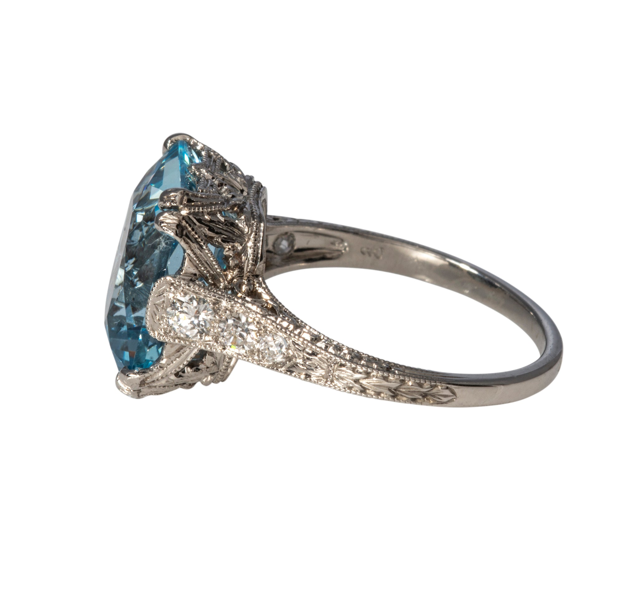 From our estate & antique collection, this Edwardian style ring features a cushion-cut aquamarine center secured by prongs. The center stone is flanked by graduated Old European cut diamonds on either side. The platinum mounting features ornate pierced filigree, milgrain, and a squared edge shank with hand engraving.  Total aquamarine weight: 5.53ct  Color: medium light, slightly grayish-blue  Clarity: eye clean  Total diamond weight: 0.38ct  Color: F  Clarity: VS  Ring size: 5.75  Weight: 5.2g