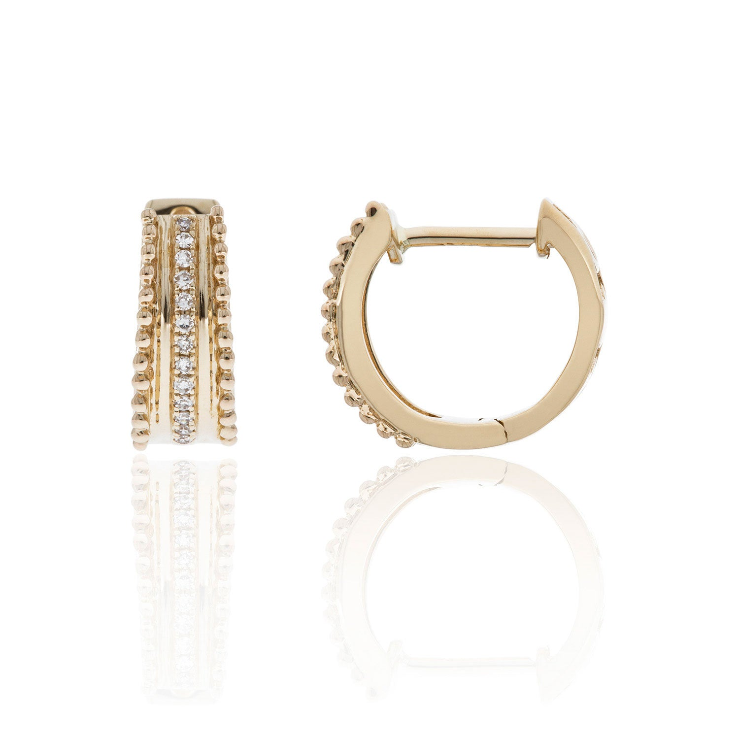 This pair of huggie hoop earrings feature a row of diamond accents flanked by beaded rows in 14K yellow gold.