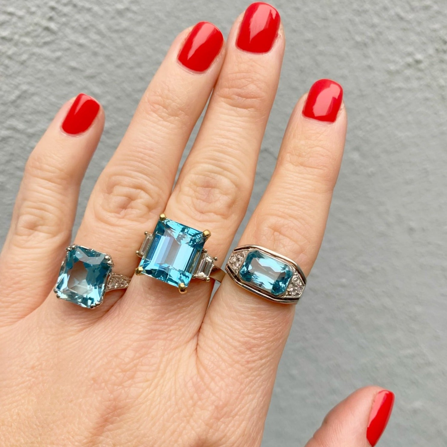From our estate & antique collection, this ring features an emerald-cut blue aquamarine center secured by yellow gold prongs. The center is flanked on either side by a prong-set trapezoid cut diamond in an 18K white gold mounting.  Total aquamarine weight: 9.04ct  Color: blue, medium tone, strong saturation  Clarity: eye clean  Total diamond weight: 1.0ct  Color: G–H  Clarity: VS  Ring size: 7  Weight: 8.5g