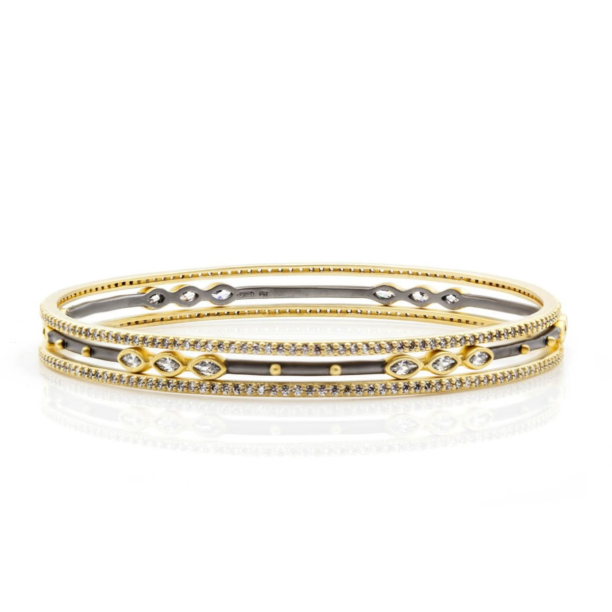"Freida Rothman Signature Marquise Station 3-Stack Bangles in yellow gold and black gold on sterling silver. This is an easy stack of bangles that have a stunning amount of sparkle.  14K yellow gold & rhodium matte finish  Sterling silver core  Hand-set cubic zirconia stones  Diameter: 2.5""   Set of 3 slide-on bangles"