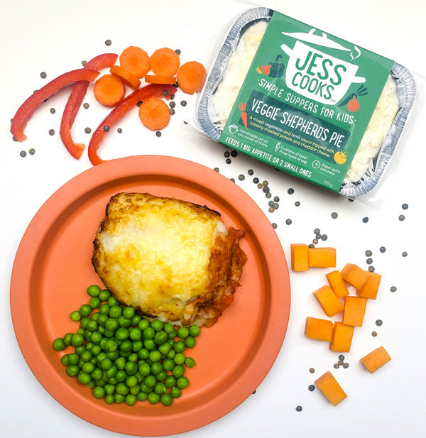 Jess Cooks Veggie Shepherd's Pie for children, surrounded by lentils and fresh vegetables, served with mashed potato and peas