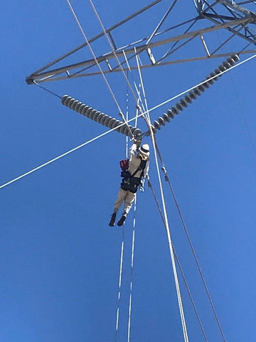 A utility lineman ascends a rope to access a hot plate on a transmission tower in rough terrain