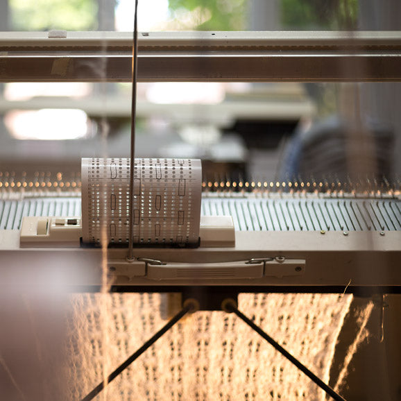 A scarf on a knitting machine.