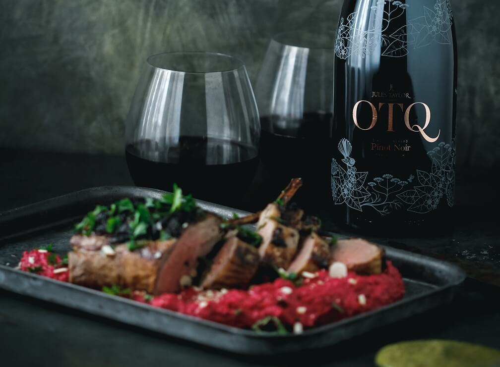 Lamb Cutlets, Beetroot skordalia and black salsa verde, with a bottle of Jules Taylor OTQ PInot Noir in the background.