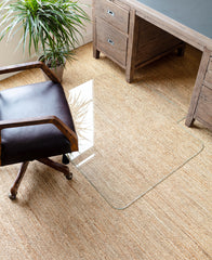 photo of a glass chair mat on a beige carpet with a black office chair next to it