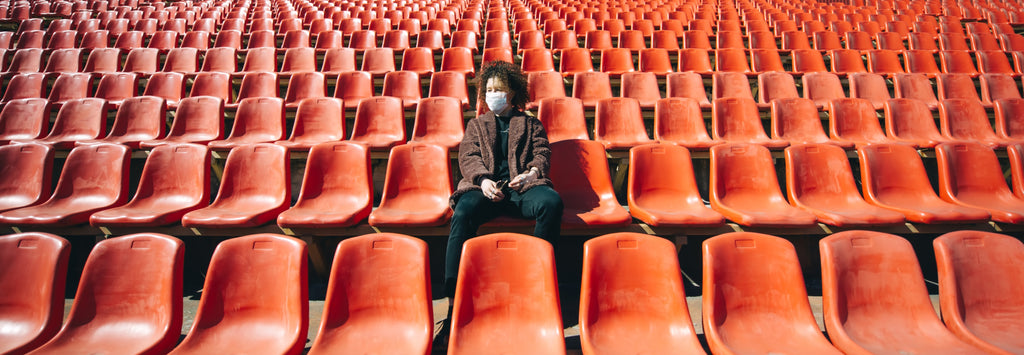 woman in medical mask sitting with smartphone on a bench in empty city stadium