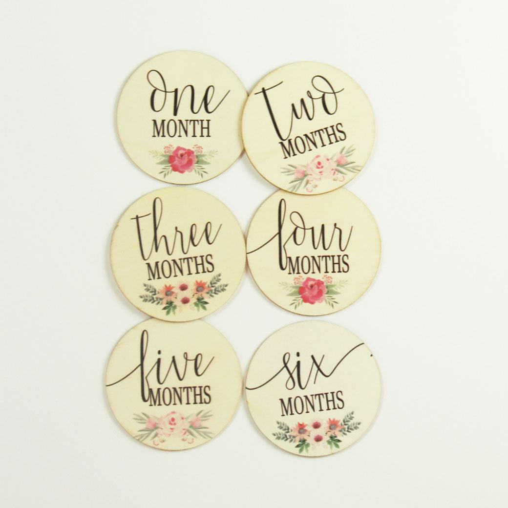 Six double-sided milestone discs with a floral design from one-month to twelve-months from Birchmark Designs