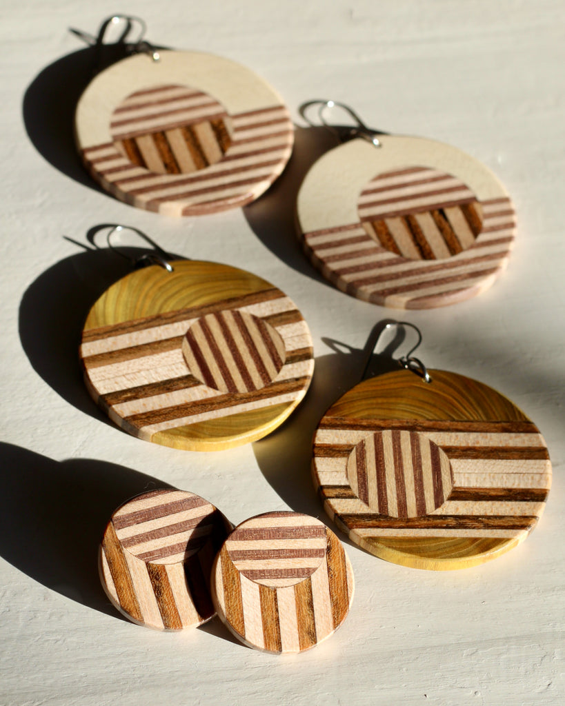 three pairs of wood earrings on white background