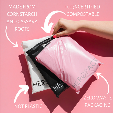 Hand holding three Hero mailers, one white, one black, and one pink, with text reading '100% Certified Compostable', Zero Waste', 'Made from cornstarch and cassava roots', and 'No Plastic.