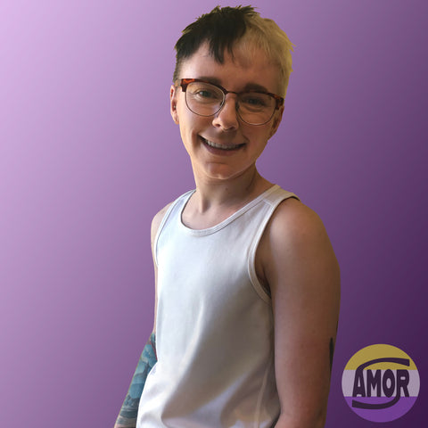 Max, a white non-binary trans person is pictured from the waist up wearing a size S, light grey racerback chest binder, that's not visible, underneath a white sports tank.
