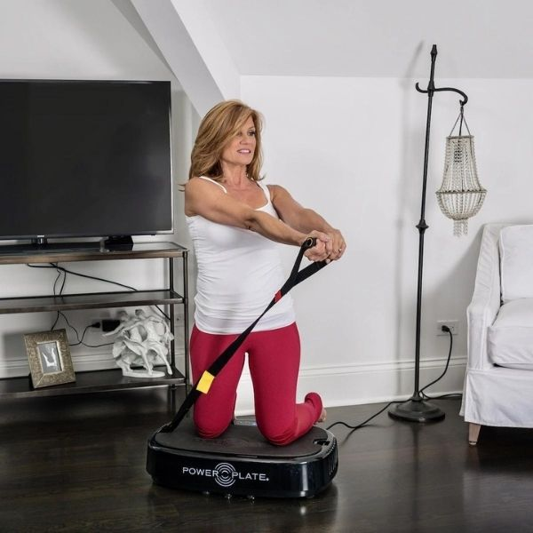 Woman doing exercise with strap on the Power Plate Personal