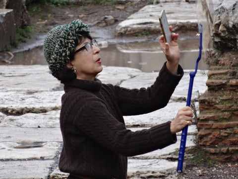 Jo, wearing a gray cap and black long sleeve top stands in an snowy landscape, using her phone to photograph a long blue stick in front of a rock formation.