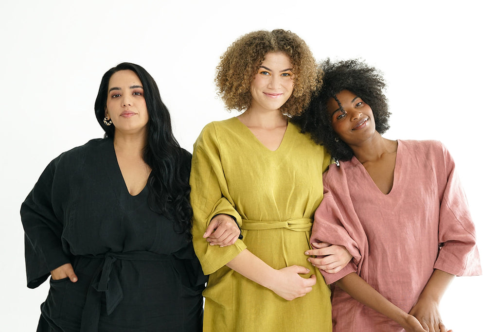 Three women shoulder to shoulder, arms linked, leaning on one another