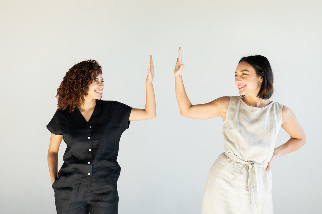 Two women side by side wearing two days off outfits holing the hands up to each other as if about to high five