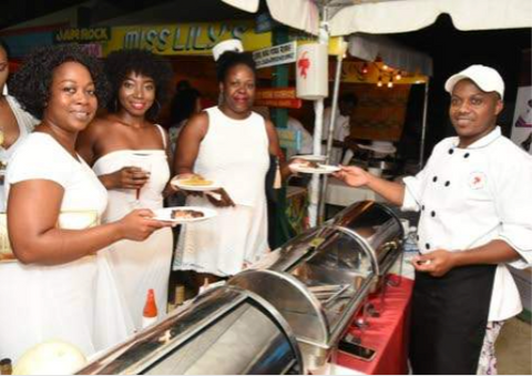 Boardwalk Village sous chef Chris Reid (right) serves up jerk chicken and pork to (from left) Novia Guthrie, Ulesia Godfrey and Crystal Foster.