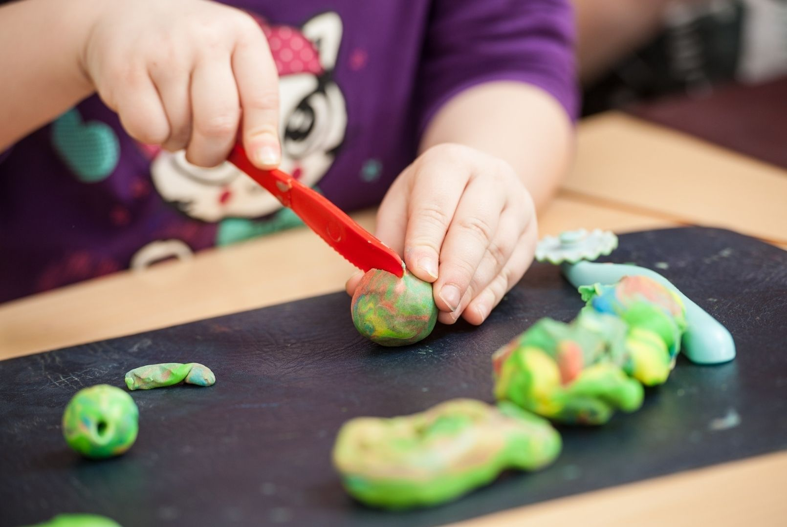 A child's hands rolling and cutting balls of playdough