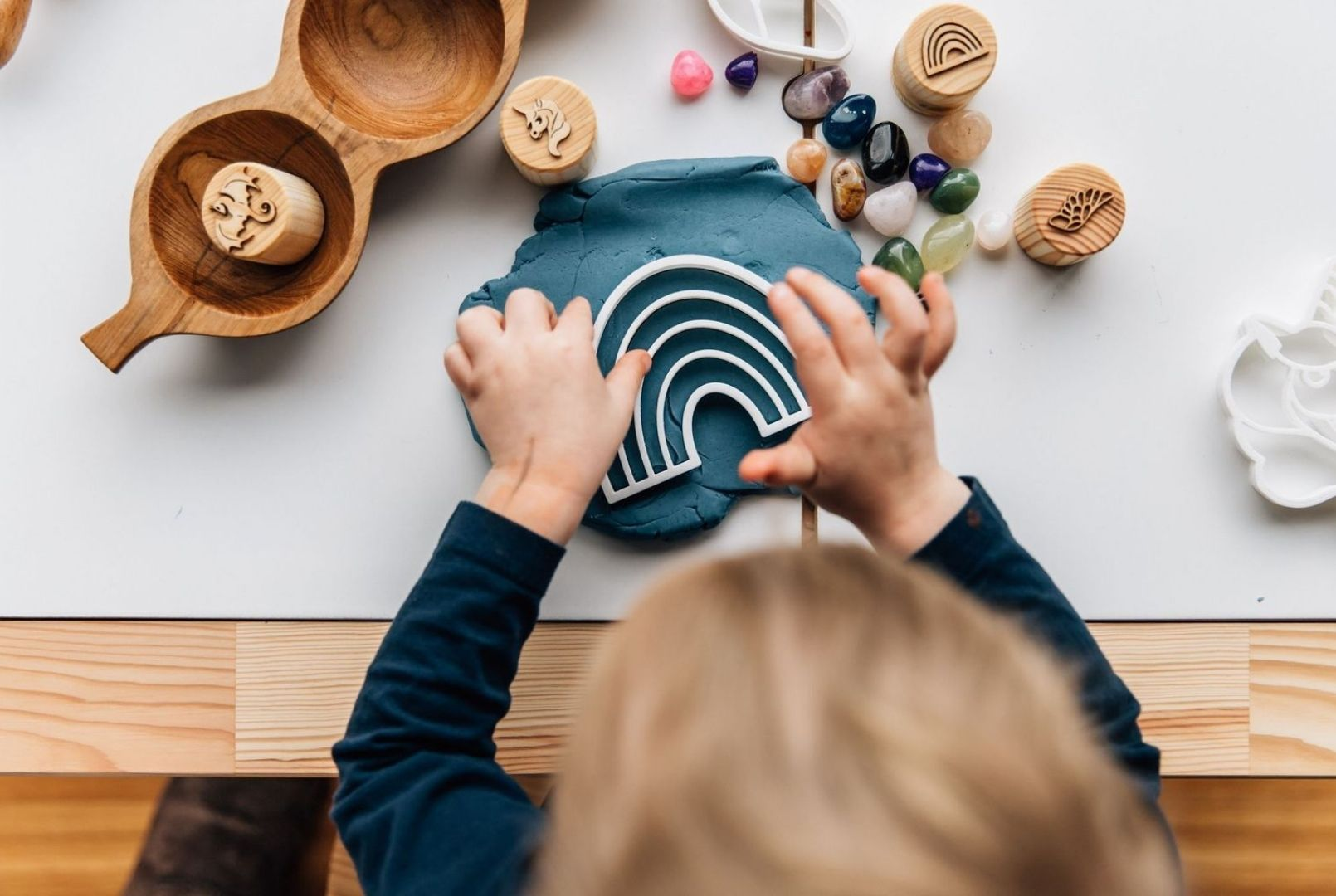 A child using bio cutters and stamps to make shapes out of blue playdough