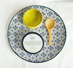 A small bowl, wooden bowl and face masks tin on a pretty plate