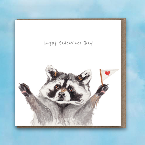 Greeting card featuring a painted raccoon with a small heart flag and text saying Happy Valentines Day