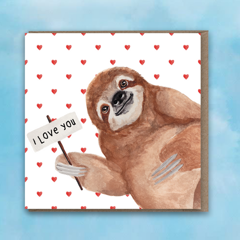 Greeting card featuring a painted sloth holding a sign saying I love you and a red heart background