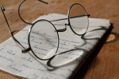 eyeglasses on top of a written paper