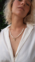 Woman in white blouse wearing short gold chain necklace beaded with shells with gold coin and acorn charms hanging from front clasp