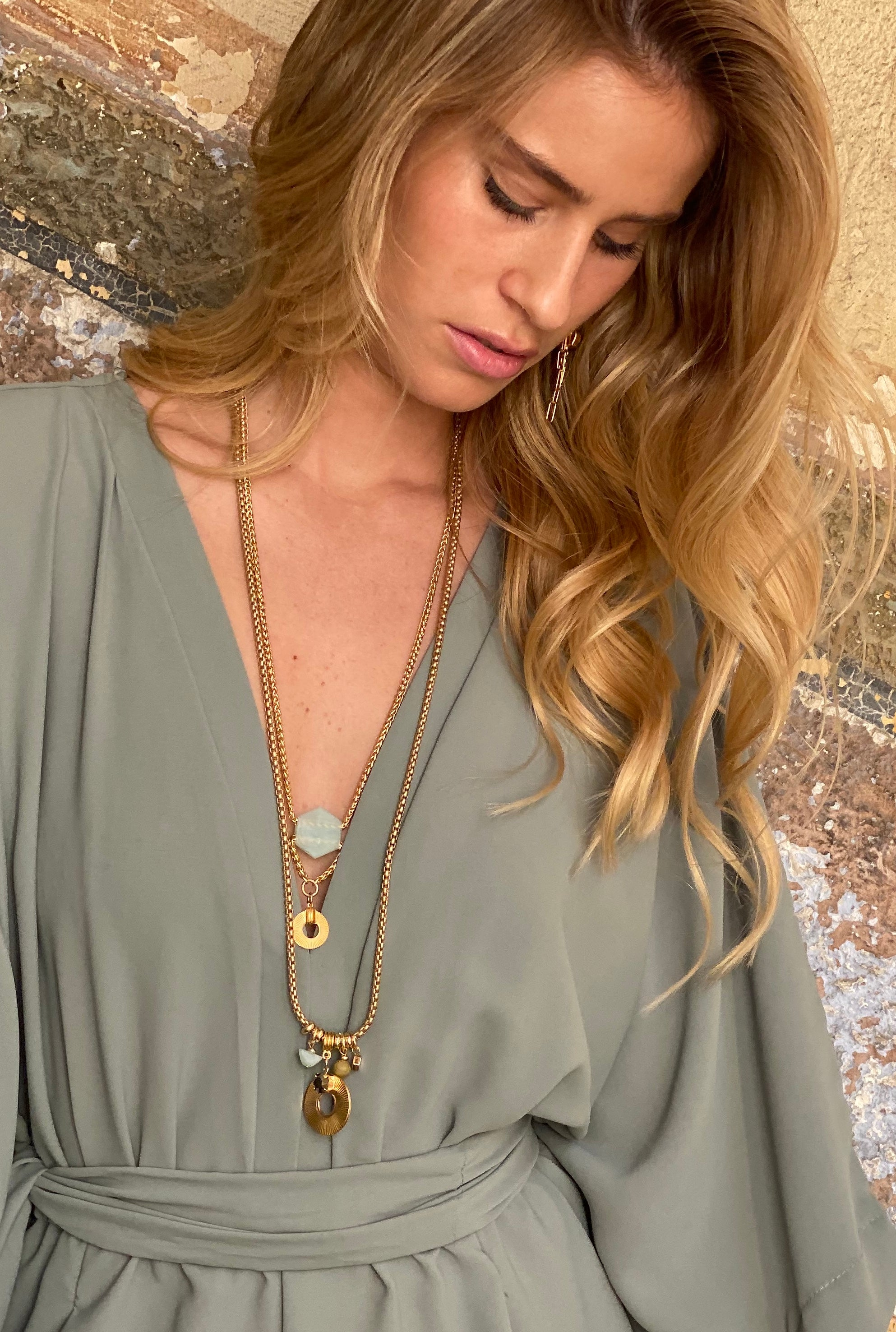Woman wearing extra long double layered thick gold chain necklace with gold disc and geometric aqua stone pendants