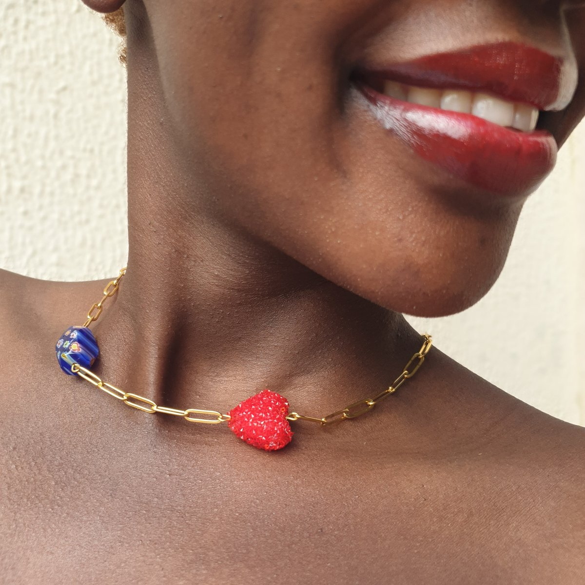 Woman wearing gold chain link choker with blue Murano glass bead and red Swarovski beaded heart