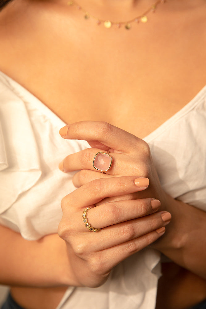 Woman wearing a two tone ring with large Rose Chalcedony stone on her middle finger and a gold band of crystal quartz the other
