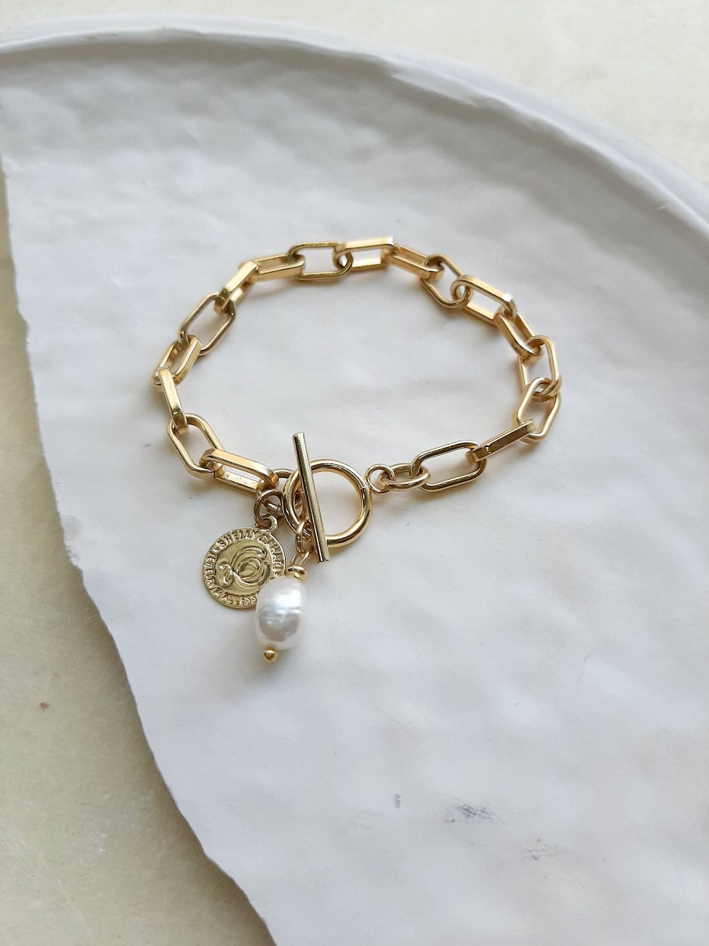 Gold chain link bracelet with bar clasp and drop pearl and gold disc charm by Shelly Dahari
